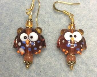Caramel lampwork owl bead dangle earrings adorned with caramel Czech glass beads.