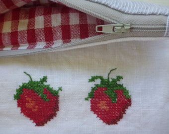 A pure linen zippered pouch, with luscious strawberries cross stitched onto white linen, lined with cheerful red and white checked linen.