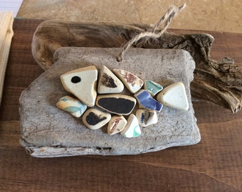 Sea pottery fish on driftwood.