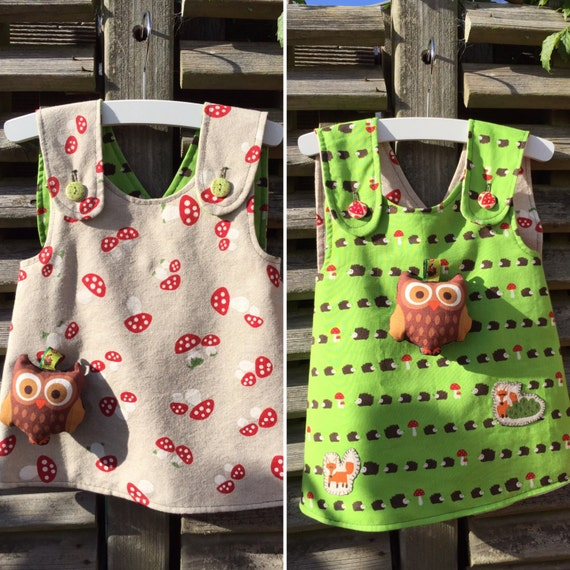 Double sided baby girl pinafore hedgehogs, two foxes and mushrooms with a toy rattle owl attatched size 74 or 6-9 months