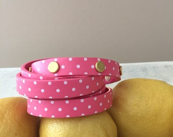 Bright pink leather wrap around bracelet with cute white polkadots.