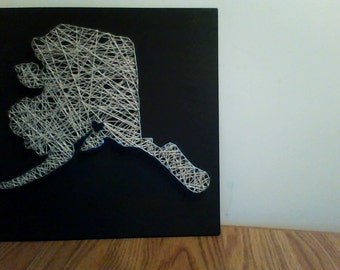 State of Alaska showing with heart for the city. Can be customized.  String art.
