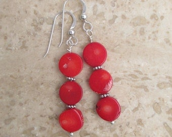 Red coral coin bead earrings with sterling silver spacer beads on a sterling silver ear wire