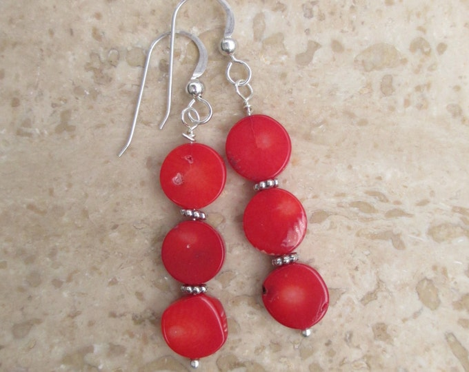 handmade red coral coin bead earrings with sterling silver spacer beads on a sterling silver ear wire