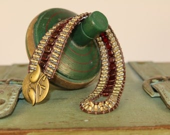 Cuff Wrap Bracelet.  Center beads dark red with gold specs.   Seed beads gold  with brown leather.  Beautiful  gold tone button.