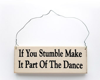 Wood Sign Saying: If You Stumble, Make It Part Of The Dance. White Wood With Black Lettering.