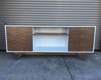 NEW Hand Built Mid Century Inspired TV Stand. Two Door w/ center shelf and angled leg base. White lacquer body w/ Walnut Doors & Leg Base.