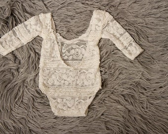 Newborn baby girl ivory floral lace long sleeved romper with low back with tiny frills incorporated in the fabric.