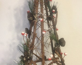 Primitive Metal Christmas Tree with berries, needles, and pine cones.
