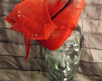 A stunning Hatinator in bright red sinamay, trimmed in feathers and swirls. Perfect for weddings, Ascot, Epsom and Kentucky Derby