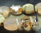 7 peach and cream pressed pebble beads with silvered ivory stringer