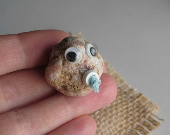 Real Pet Rock baby with glasses and pacifier with burlap pillow