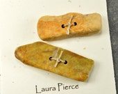 A pair yellow tan stick shaped natural  rustic Maine sea stone toggle buttons great  for all fiber artists and knits