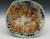 love bowl in a rainbow of color red orange green blue yellow black tan terra cotta