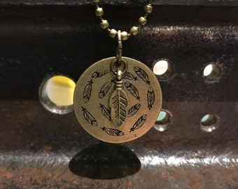 Hand stamped feather brass disk necklace.