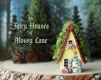 The Fairy Houses of Mossy Lane - Handcrafted Cottage in Pastel Yellow w/ Moss Covered Shingled Roof, Blooming Flower Boxes and Wooden Door