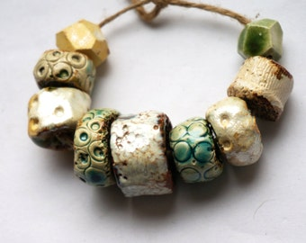 The clear body of spring -- a set of 9 iridescent/faceted/turquoise/brown  ceramic art beads