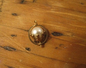 Pearl  that spins on an axis.  pendant / charm with patina.