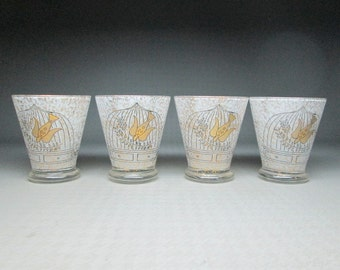 four glasses GEORGES BRIARD bird and cage , black and gold on clear glass with white interior .
