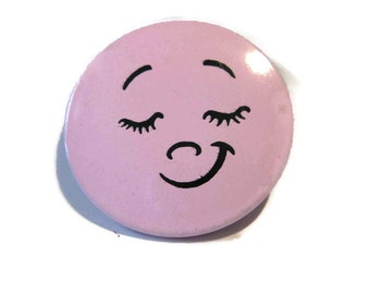 pinback button, pink smiley face, pleased? smug? sweetly shy?