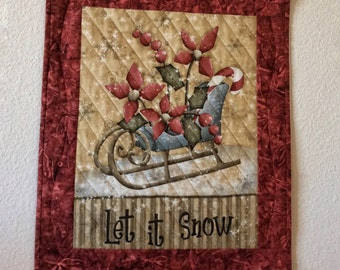 Quilted Winter Wall Hanging with cranberry flowers in a snow bladed sleigh..Cranberry..Green..Beige..White