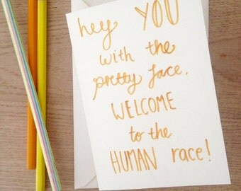 Hand drawn New Baby Card. Welcome to the Human Race! ELO lyrics. Available in Yellow, Pink or Blue. Hand lettering. (Blank Inside)