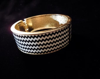 Vintage Mod Bracelet in black and white chevron pattern with gold toned metal trim for accent. Fantastic bold clamper style bracelet.