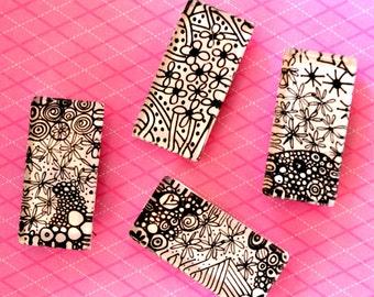 Doodle Magnet Set. Four rectangular black and white magnets.