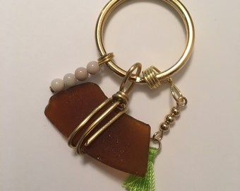 Gold nein green tassel and fossil keychain
