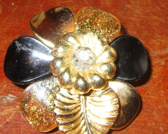 "vintage goldtone/black plastic floral brooch 2""across pin has been reglued"