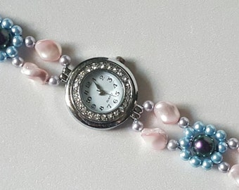 Round silver watch wrapped by crystals and a band of rosaline, light blue, lavender, and iridescent purple Swarovski crystal pearls
