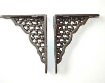 A pair of small cast iron honeycomb shelf brackets