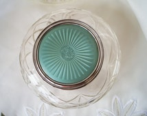 An iconic art deco cut glass over sized powder bowl with a green faux enamel guilloche lid. Very collectible.