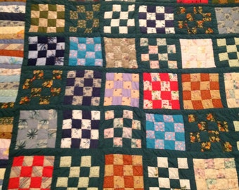 A true heirloom! Handstitched patchwork quilt with square block design in various colors borederd in green.