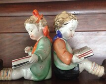 """Porcelain bookends -- Japanese """"Hummel"""" figurines of boy and girl reading"""