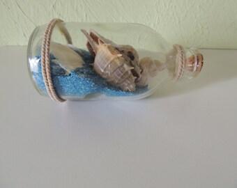 Art glass bottle, Mediterranean shells and sand