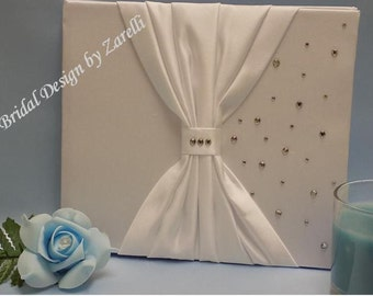 Wedding guest book in White or Ivory. Satin with bow shaped sash detail and scattered diamantes. Also has space for names and dates