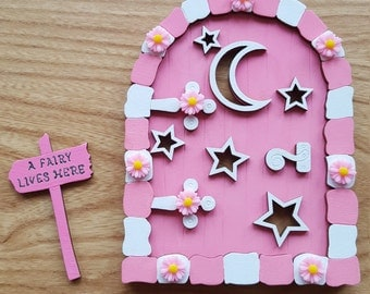 Pink Fairy Door with flowers and sign post.