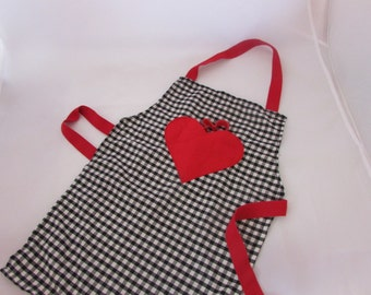 Childs apron in black and white gingham fabric.