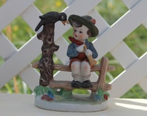German Hummel Style Vintage Hand-Painted Porcelain Bisque Figurine of Young Boy on Fence with Black Crow