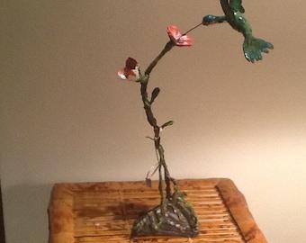 Hummingbird on the air feeding on a flower with pedestal. Art 21