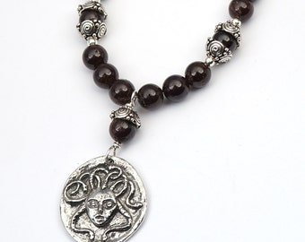 Medusa necklace with dark red garnet beads, mythic theme ouroboros, 19 1/2 inches long