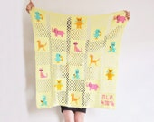 1976 pastel yellow baby blanket . animal babies . crocheted granny squares