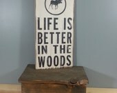 Life is Better in the Woods, circle with moose, hand painted, distressed, wooden sign.  blue with white and black