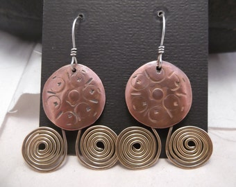 textured copper circle with two brass spirals. Silver ear wire