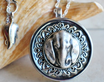 Elephant music box locket, round  locket with music box inside, in silver tone with filigree and elephant on front cover.