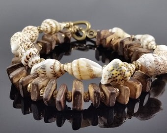 Double stranded bracelet with wood bead, shells, and brass accents.