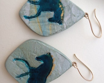 Turquoise trotting horse through the woods.  Dangle polymer clay earrings.