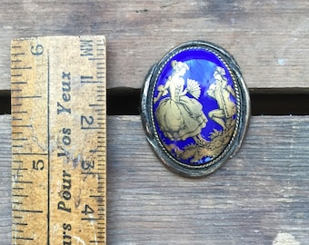 Vintage blue glass brooch with detailed romantic image