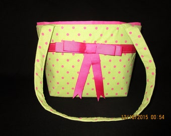 Green and pink polka dot purse with a ribbon and bow